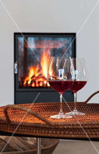 Two glasses of red wine on a table in front of a fireplace