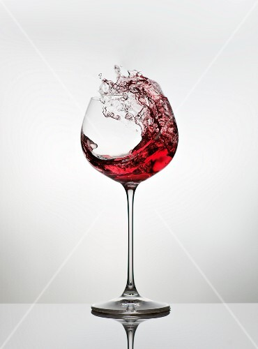 Red wine spattering out of a glass