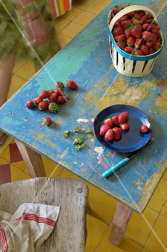 Strawberries on blue plate and in punnet on vintage wooden table