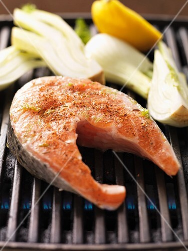 Raw spiced salmon steak and fennel on the barbecue