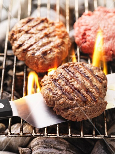 Beefburgers on the barbecue (raw and cooked)