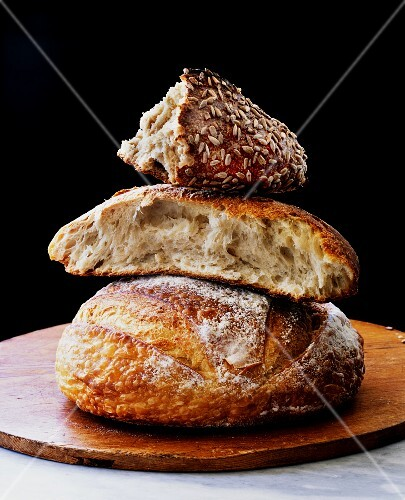 An assortment of sour dough breads, stacked