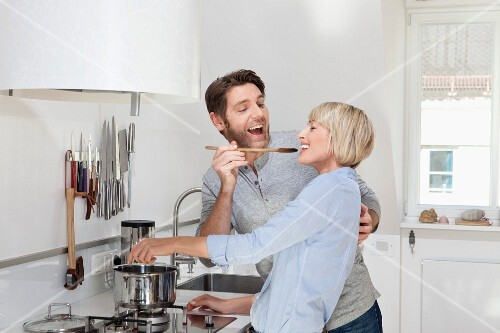 Germany, Bavaria, Munich, Mature woman cooking food while man feeding