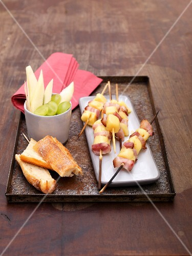 Grilled cheese and bacon kebabs, grapes, apples and bread