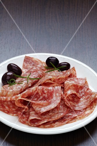 Slices of salami with olives on a plate