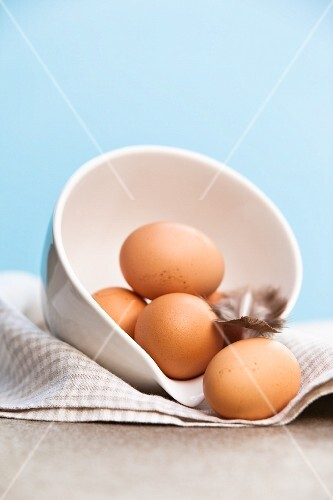 Brown chicken eggs in a bowl with a feather