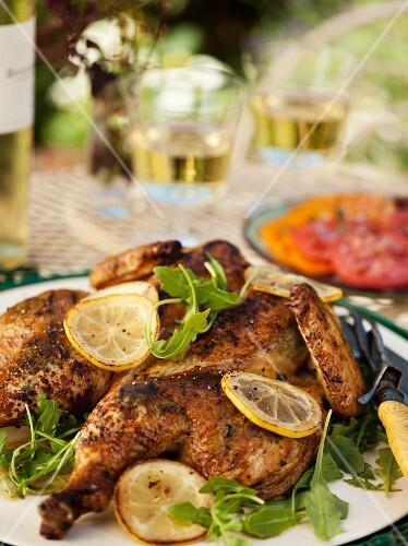 Grilled Butterflied Chicken with Lemon and Herbs on an Outdoor Table