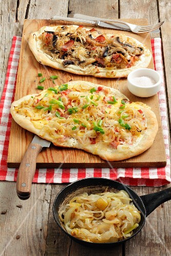 Two tarte flambées (one with sauerkraut, mushrooms and bacon and one with onions, cheese and bacon)
