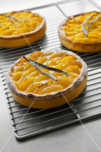 Apple and vanilla tartlets on a cooling rack