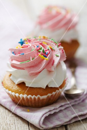 Cupcake with cream, raspberry cream and colorful sugar sprinkles