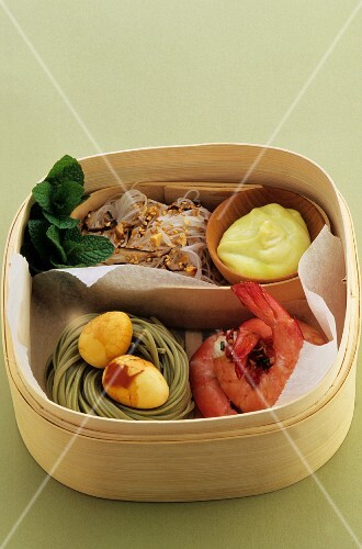 Rice noodles, quail's eggs in a nest of noodles, and prawns, all in a bamboo basket