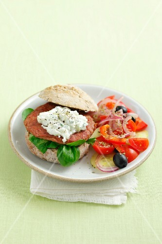 A burger topped with tzatziki, served with Greek salad