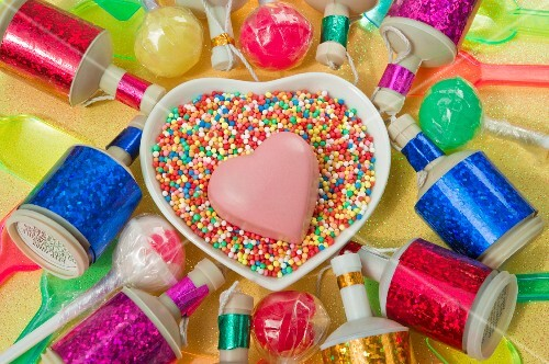 overview still life close up of heart dish with a pink chocolate heart shape and coloured party poppers and plastic ice cream spoons