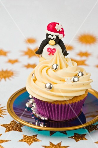 still life of a Christmas marzipan penguin sitting on top of a cream cup cake with gold star pattern on table