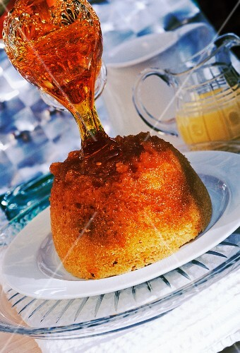 golden syrup poured onto a steamed pudding