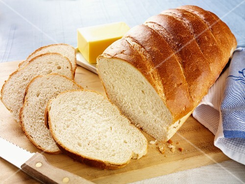 A white loaf, baked in a tin, with some cut slices
