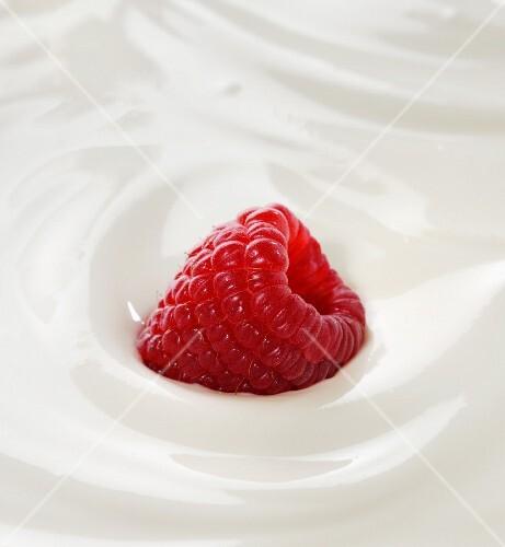 A raspberry in yoghurt (close-up)