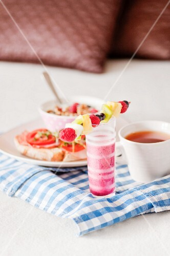 A breakfast tray with a cup of tea and a raspberry smoothie
