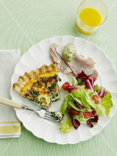 A slice of spinach quiche on a plate with ham and salad