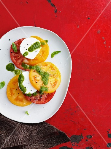 Red and yellow tomatoes with mozzarella and pesto