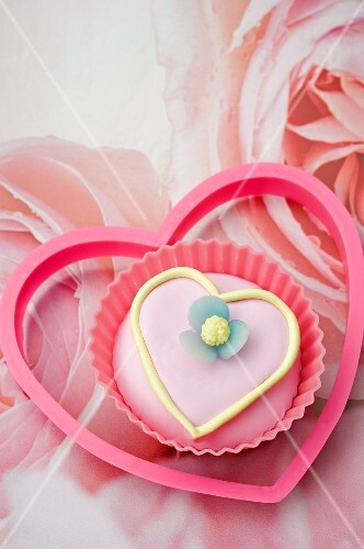 close up of one pink iced, love heart shaped cup cake with a pink plastic heart shape biscuit cutter