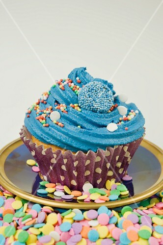 close up of single blue iced cup cake decorated with sprinkles and sweets with a white background