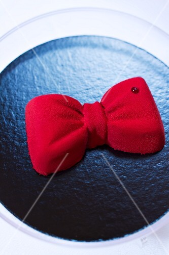 A chocolate cake topped with a red ribbon