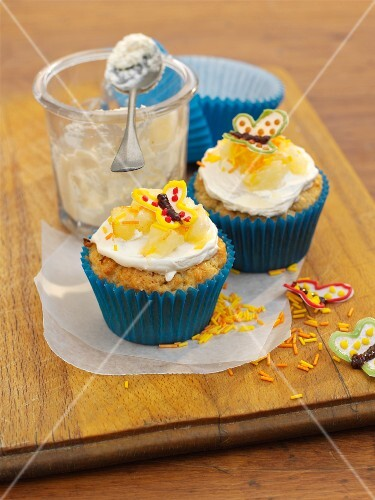 Cupcakes topped with pineapple and a butterfly decoration