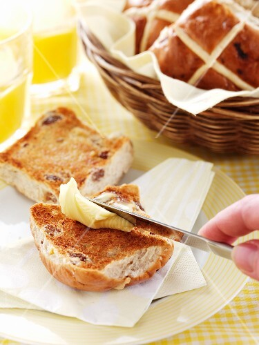 A hand spreading a hot cross bun with butter
