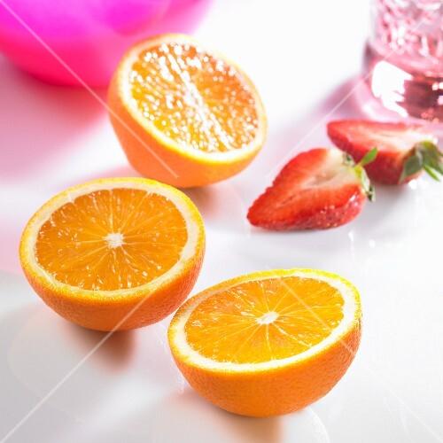 Three orange halves and strawberry halves