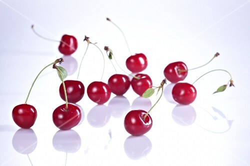 Several sour cherries with stalks and leaves