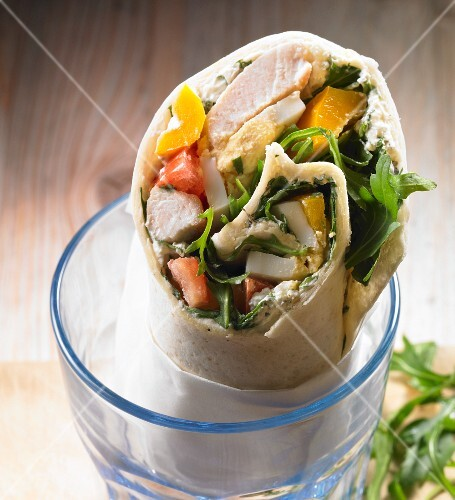 A wrap with chicken, yellow pepper, tomato, rocket, egg and cream cheese