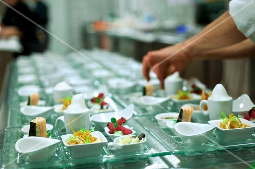 A chef arranging starters on a buffet