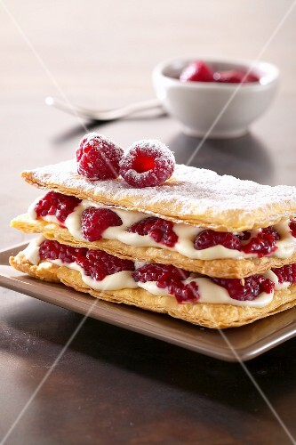 Slices of puff pastry layered with cream and raspberries