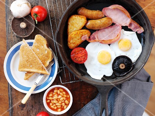 English breakfast with fried eggs, bacon, small sausages, baked beans and toast