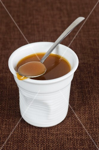 Caramel sauce in a pot with a spoon