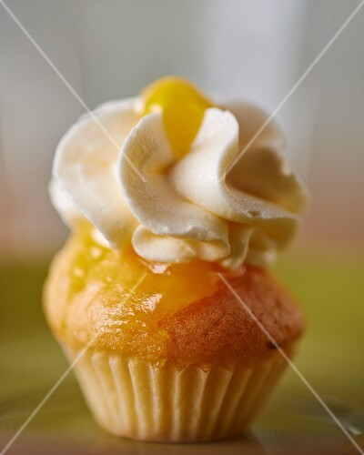 A cupcake topped with vanilla cream icing and lemon curd
