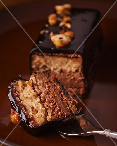 A chocolate cake with nuts, one slice cut