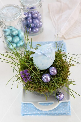 An egg decorated with a ribbon and chocolate eggs in an Easter nest made of moss and grass