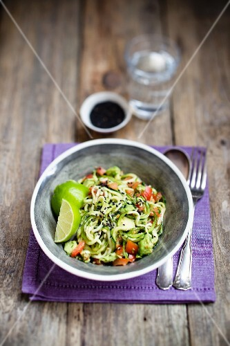 Raw courgette spaghetti with tomatoes, sesame seeds and limes