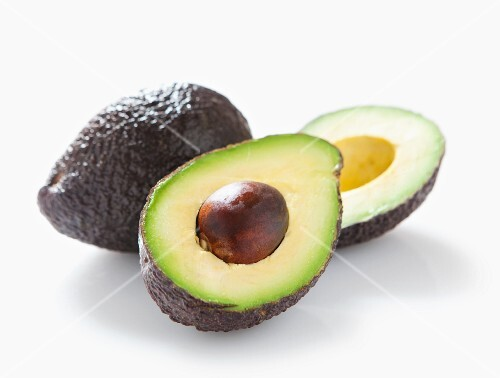 A whole and a halved avocado with no background