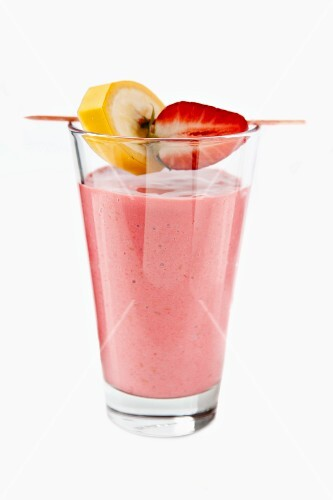 A strawberry smoothie with banana and strawberry pieces on a cocktail stick