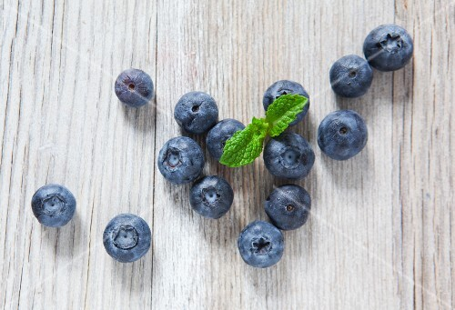 Blueberries and mint on a wooden slab, from above