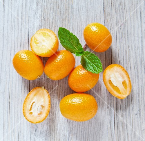 Kumquats on a wooden slab with mint, viewed from above
