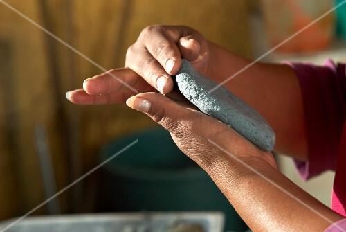 Hands shaping tlacoyo (oval corn tortilla, Mexico)