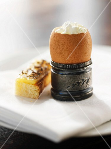 An Egg with Whipped Cream in an Egg Cup; Slice of Bread Topped with Cheese