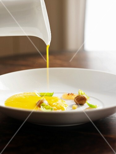 Pouring Smooth and Creamy Squash Soup into a White Bowl with Garnishes