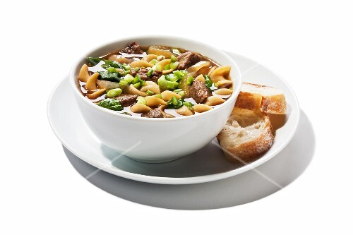 A Bowl of Bourbon Beef and Noodle Soup with Two Slices of Bread; White Background