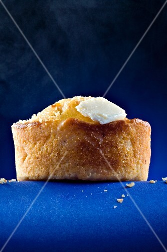 A Corn Muffin with Butter on Blue