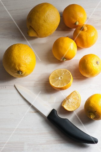 Bergamots and meyer lemons, whole and cut, with a ceramic knife on a white wooden background